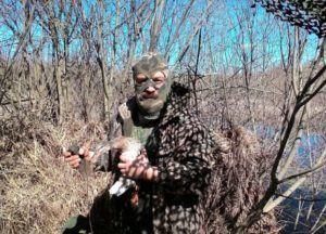 Охотник с подсадной уткой в кустарнике